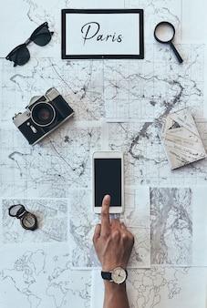 新しい目的地を計画しています。地図の前でスマートフォンを使用して男の上面図をクローズアップ