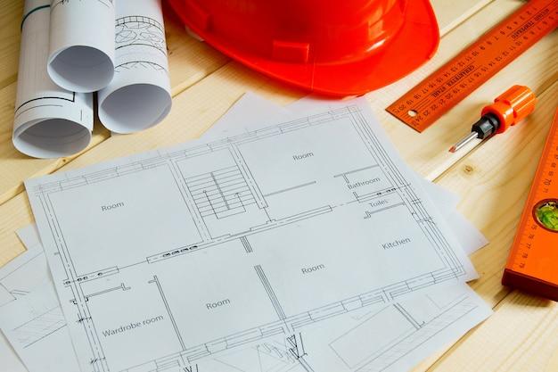 Планировка строительства дома. ремонтные работы. рисунки для строительства, шлема, карандашей и других инструментов на деревянном фоне.