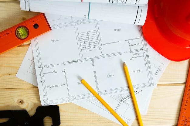 家の建設の計画。修理作業。木の表面にある建物、ヘルメット、鉛筆、その他の道具の図面。