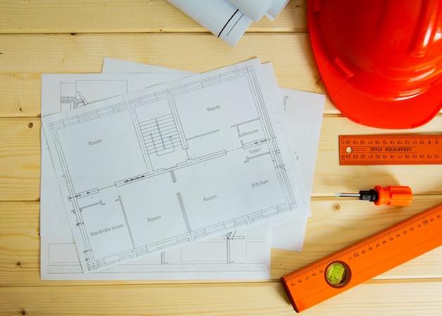 Планировка строительства дома. ремонтные работы. рисунки для строительства, каски, карандашей и других инструментов на деревянной поверхности.