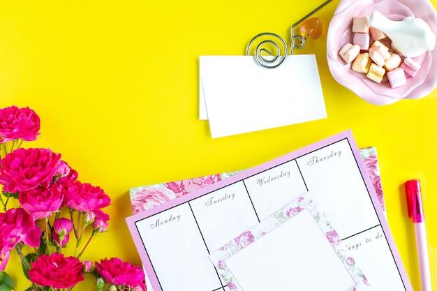 Планирование важных вещей, розовые письменные принадлежности на цветном фоне. дела, которые необходимо сделать. вид сверху. копировать пространство