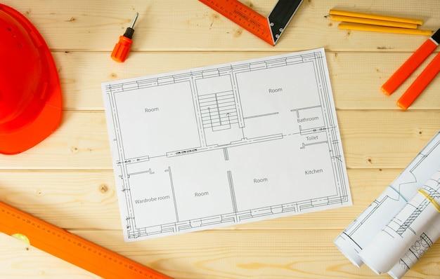 アパートの修理の計画。修理作業。木製の背景に建物、ヘルメット、鉛筆、その他のツールの図面。