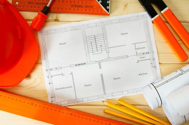 Планировка ремонта квартиры. ремонтные работы. рисунки для строительства, шлема, карандашей и других инструментов на деревянном фоне.