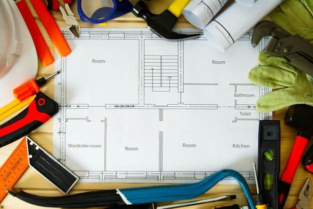Планирование ремонта дома. строительство дома. рисунки для строительства и многие другие инструменты на деревянном фоне.