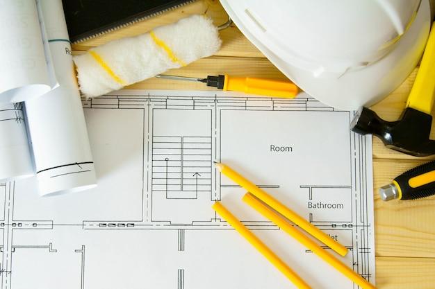 집 수리 계획. 수리 작업. 나무 배경에 건물, 톱, 망치 및 기타 도구에 대한 도면.