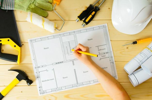 家の修理の計画。修理作業。木製の背景に建物、女性の手、のこぎり、その他のツールの図面。