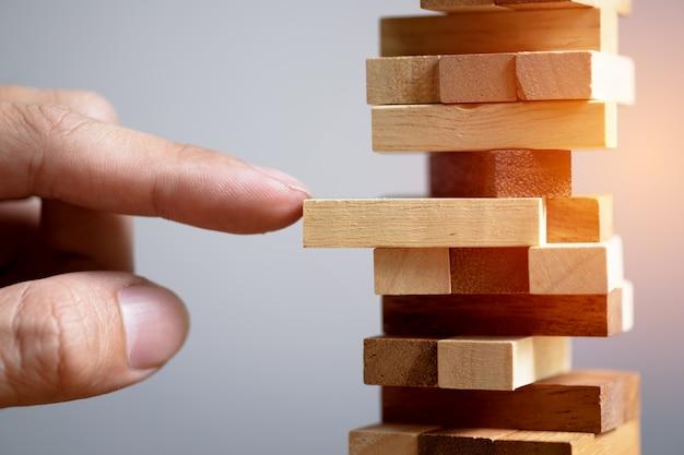 Планирование, риск и стратегия в бизнесе, бизнесменах и инженерах, играющих в азартные игры, размещение деревянного блока на башне.
