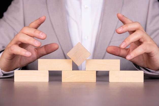사업 계획, 위험 및 전략, 사업가 도박 타워에 나무 블록 배치