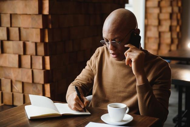 Планирование дня. спокойный темнокожий студент пишет расписание уроков в тетради, сидя в современном баре, пустое место
