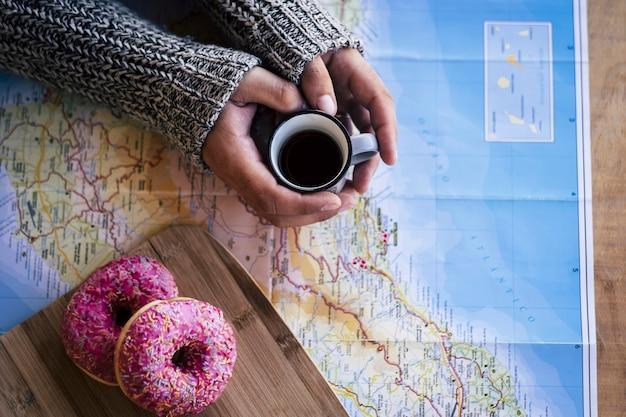 새롭고 멋진 하루를 시작하기 위해 아침 아침에 다음 휴가지 여행을 계획합니다. 커피와 세계지도에 한 쌍의 달콤한 도넛. 손을 잡고 카페를 찾고 장소
