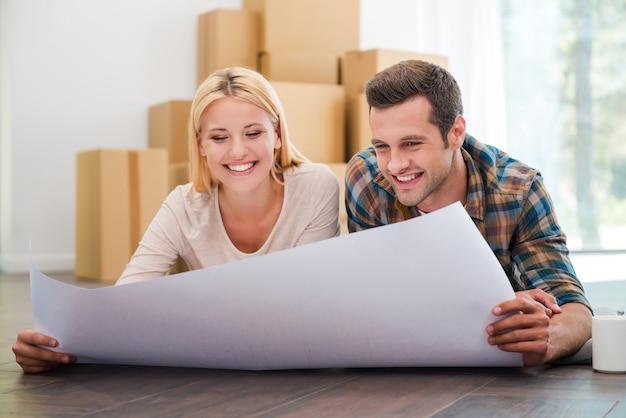 새 집을 함께 계획합니다. 즐거운 젊은 부부는 새 아파트 바닥에 누워 청사진을 들여다보며 마분지 상자를 배경으로 깔고 있습니다.
