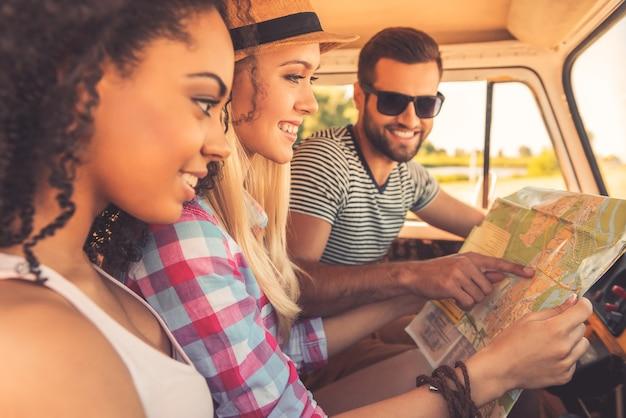 Планируем поездку. вид сбоку трех веселых молодых людей, изучающих карту и улыбающихся, сидя в своем минивэне