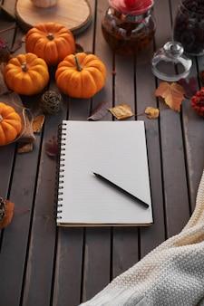 リストを行うことを計画しています。カボチャ、ナナカマドと葉と木製のテーブルの上の秋の気分の構成。赤いカップと灰色の木製テーブルでメモ帳とブラックコーヒーを開き、温かい飲み物