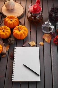 リストを行うことを計画しています。カボチャ、ナナカマドと葉と木製のテーブルの上の秋の気分の構成。ペンとブラックコーヒーでメモ帳を開く