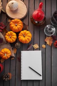 リストを行うことを計画しています。カボチャ、ナナカマドと葉と木製のテーブルの上の秋の気分の構成。