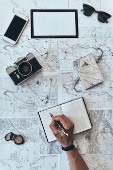 旅行の計画。サングラスで日記に何かを書き留める男の上面図を閉じる