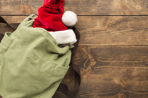 Planning for travel concept. vintage backpack with santa claus hat on wooden table. .