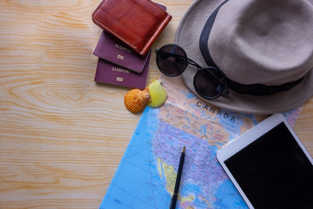 Planning vacation with other travel accessories on wooden, travel concept background