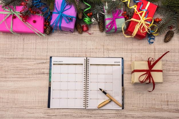 새해 계획입니다. 선물 상자와 전나무 가지가 있는 탁자 위에 열린 일기