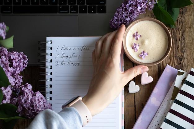 Планы на день с чашкой кофе. красивый фон с кофе и сиренью.