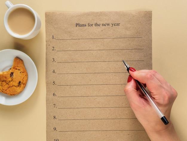 新しい年の計画。女性の手に黒いボールペン。