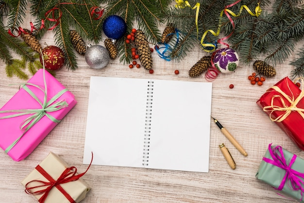 Plans for new year. open diary on table with gift boxes and fir branches
