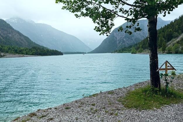 Летний пейзаж plansee с крестом под деревом (австрия)