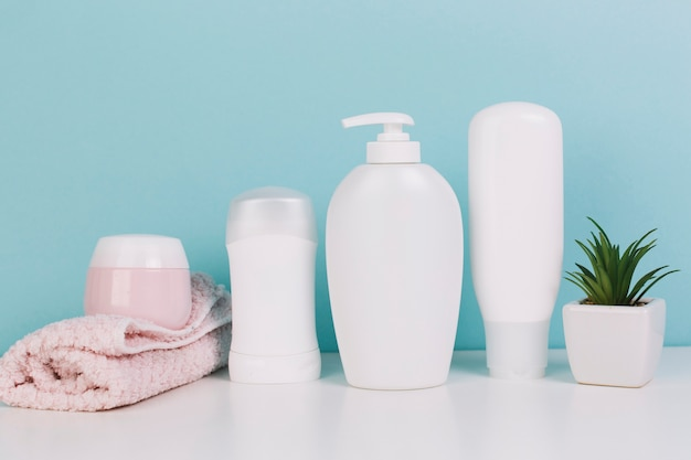 Завод и полотенце возле косметических бутылок