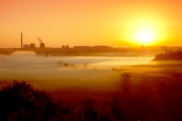 Завод на рассвете, в сумерках закат, восходящее солнце, с утренним туманом и черными силуэтами