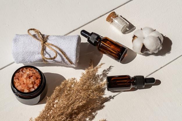 植物ベースのフェイシャルリラクゼーションセット。ドライフラワーリードの小枝、アロマボトル、スパタオル、木製テーブルのスキンケアエッセンシャルオイル