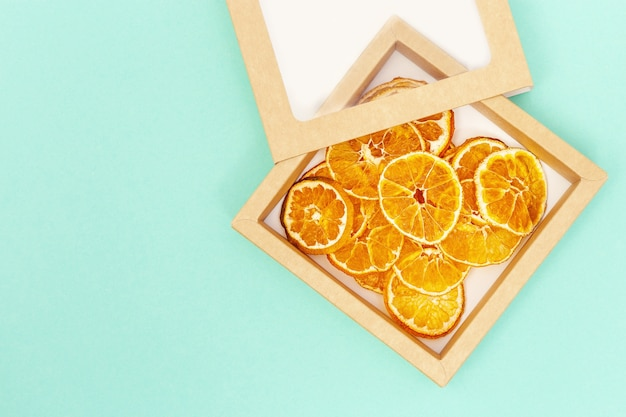 Plant based food concept. dehydrated fruit chips of tangerine, rounds slices as healthy snack or sweets.
