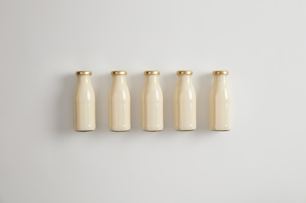 Plant based nut vegan milk in five glass bottles on white background. vegetarian beverage as alternative to dairy product made of grains, legumes, nuts, seeds. vegetable milk advertising concept