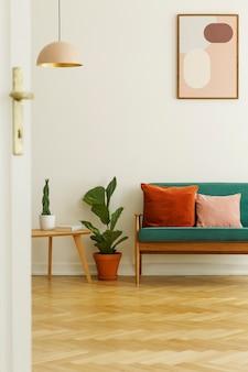 ポスターとランプ付きの明るいリビングルームのインテリアのテーブルと緑のソファの間に植えます。本物の写真