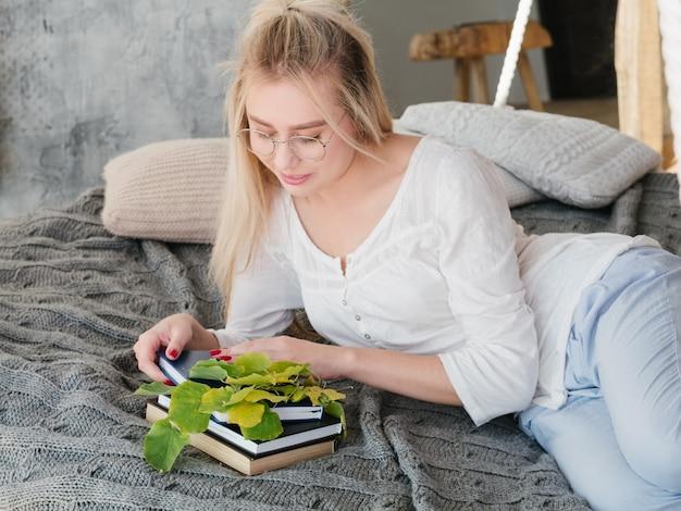 植物生物学者の余暇。自宅の居心地の良いベッドで本を読んでいる眼鏡の女性科学者の肖像画。