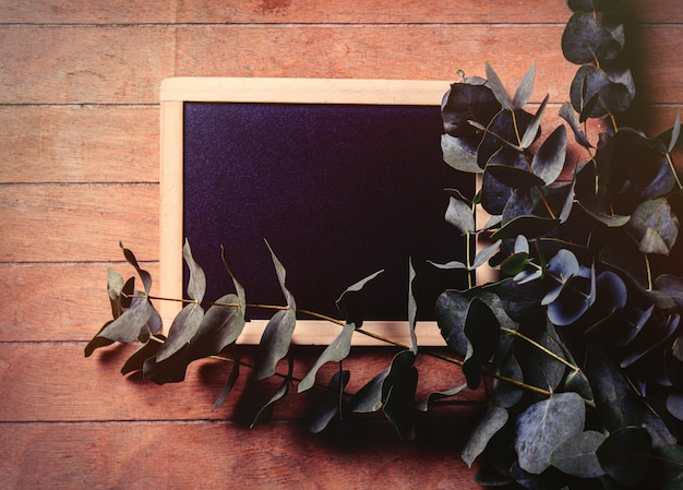 Plant and blackboard on a wooden table. above view