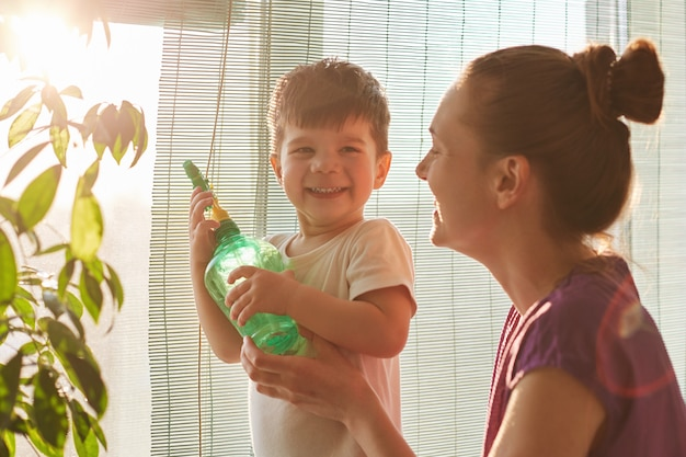 Plant care concept. cheerful little male kid holds spray bottle, wants to water flower, stands neear his affectionate mother near window at home. young mum and her son spray plant indoor together