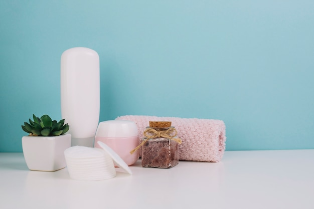 Plant and cosmetics bottles near towel and cotton pads