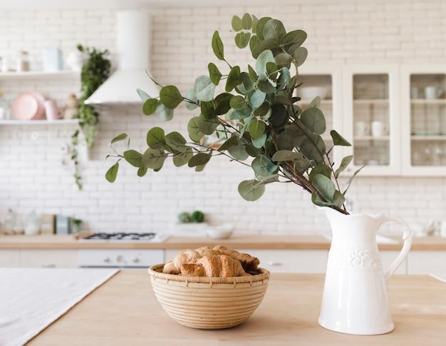 Pianta la decorazione sul ripiano del tavolo in cucina moderna luminosa