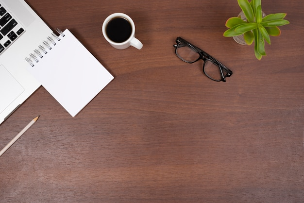 Plant; eye glasses; tea; blank spiral notepad and pencil with laptop on wooden desk