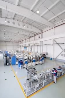 車のヘッドライトの製造と組み立てのための工場自動車部品を製造する労働者