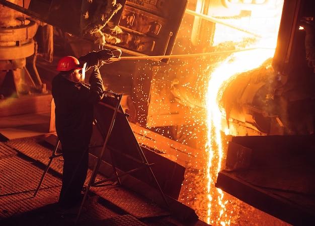 Завод по производству стали. электроплавильная печь. заводской рабочий берет образец на металл.