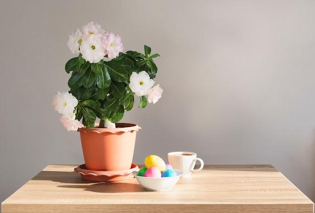 나무 테이블과 흰색 배경 위에 다채로운 부활절 달걀과 냄비에 공장.
