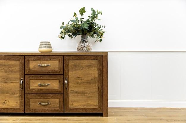 Растение в вазе на деревянной мебели