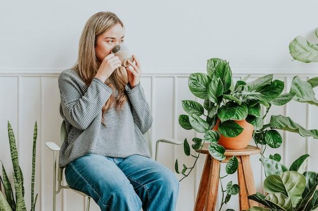 彼女の植物の隅で休んでお茶をすすりながら植物の女性