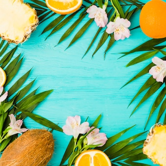 Plant leaves and exotic fruits near flowers