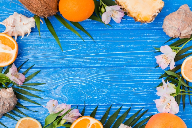 Plant leaves and fruits near flowers with seashells