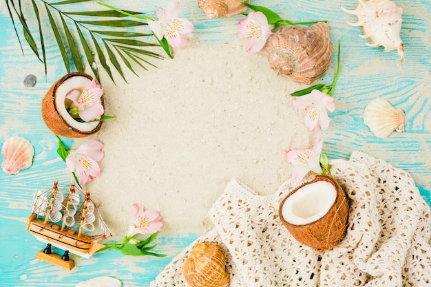 Plant leaves near coconuts and flowers with seashells on board