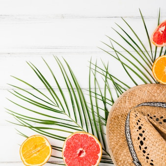 Plant leaves near fresh exotic fruits and hat on board