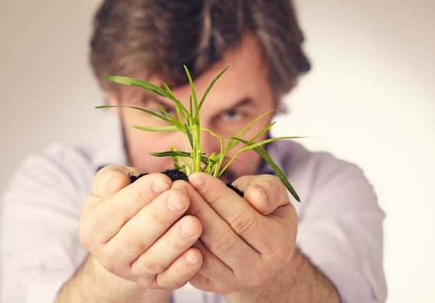 A plant in man hands against white surface
