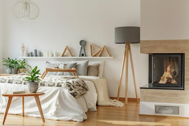 Растение на деревянном столе и серая лампа в теплом интерьере спальни с камином возле кровати